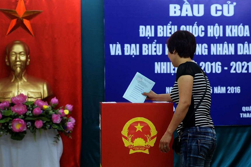 A woman casts her ballot at a local voting station in Hanoi on May 22, 2016.