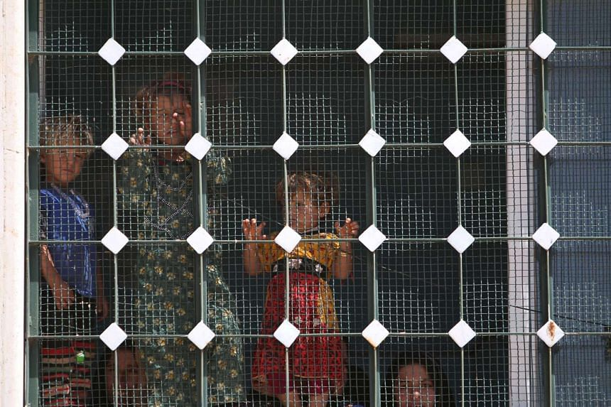 Women and children that fled Manbij city stand inside a building after arriving in the areas that Syria Democratic Forces (SDF) alliance forces took control of, on June 8, 2016.