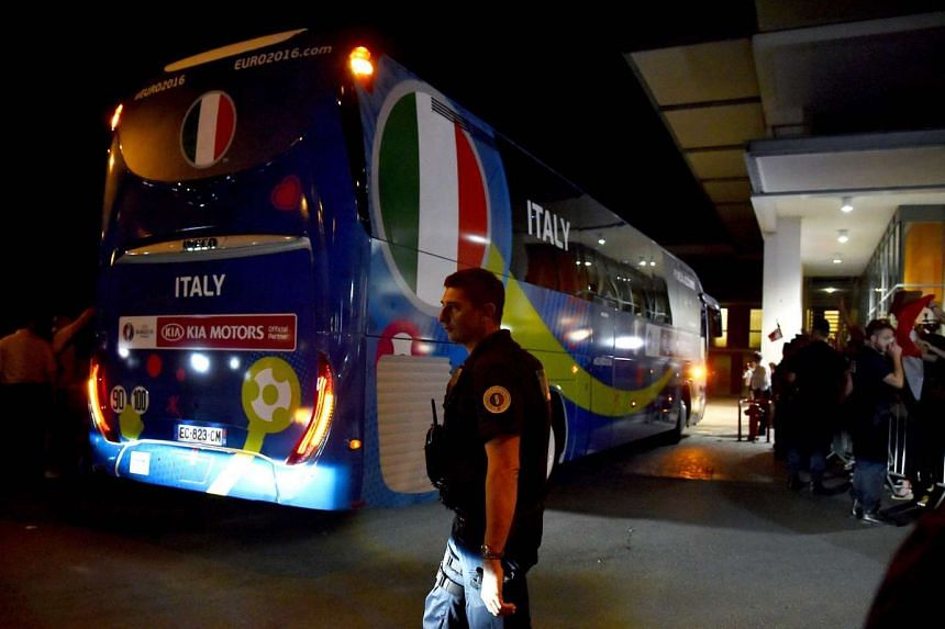 A French policeman stands guard as the bus of the Italian national football team arrives at the Marriot hotel in Montpellier on June 8, 2016.