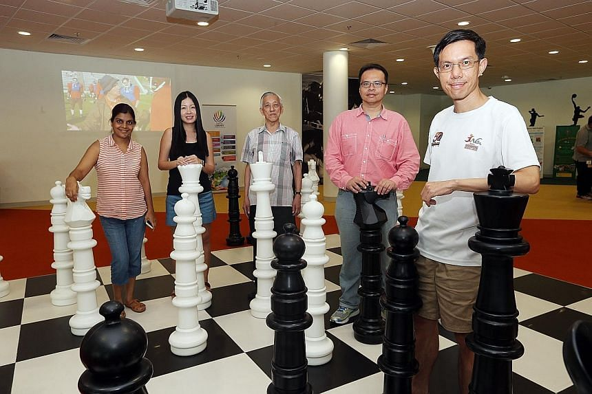 """Chess mums"" (from left) Aarti Agarwal and Esther Koh, international chess master Giam Choo Kwee, SCF president Leonard Lau and ""chess dad"" Chan Wei Hsien at the Sports Hub Library. The efforts of chess enthusiasts and parents are drawing new young p"