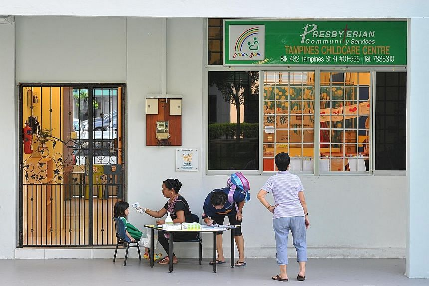 Assistant teacher Kalaichelvi Shanmugam, 49, checking a child's temperature and looking out for blisters before allowing her to enter a childcare centre in Tampines yesterday. Singapore could be heading for one of its worst hand, foot and mouth disea