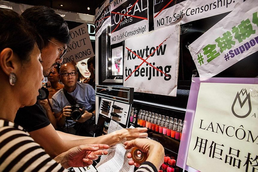 Protesters displaying posters at a Lancome outlet in a shopping mall after the cosmetics giant cancelled a concert featuring pro-democracy singer Denise Ho.