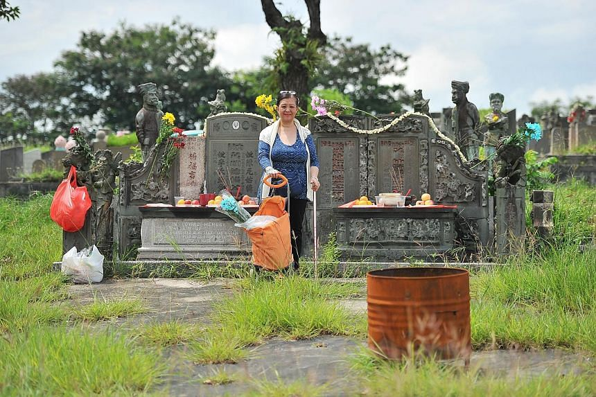 Ms Yeo beside the mass grave of four of her ancestors, which is flanked by statues of Sikh guards and Chinese military warriors, at Choa Chu Kang Cemetery. The wealthy Yeo family moved here from China and Semarang in Indonesia in the late 1800s.