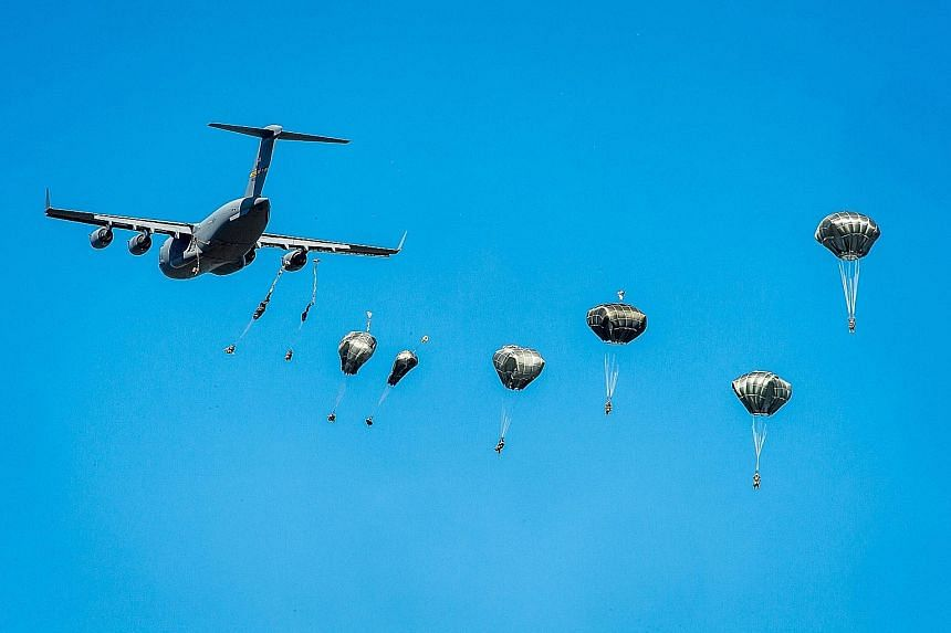 A United States Army C-17 Globemaster military transport plane dropping US paratroopers from the 82 Airborne Division during the Swift Response-16 exercise at a military area near Torun, Poland, on Tuesday. About 2,000 paratroopers from Poland, the U