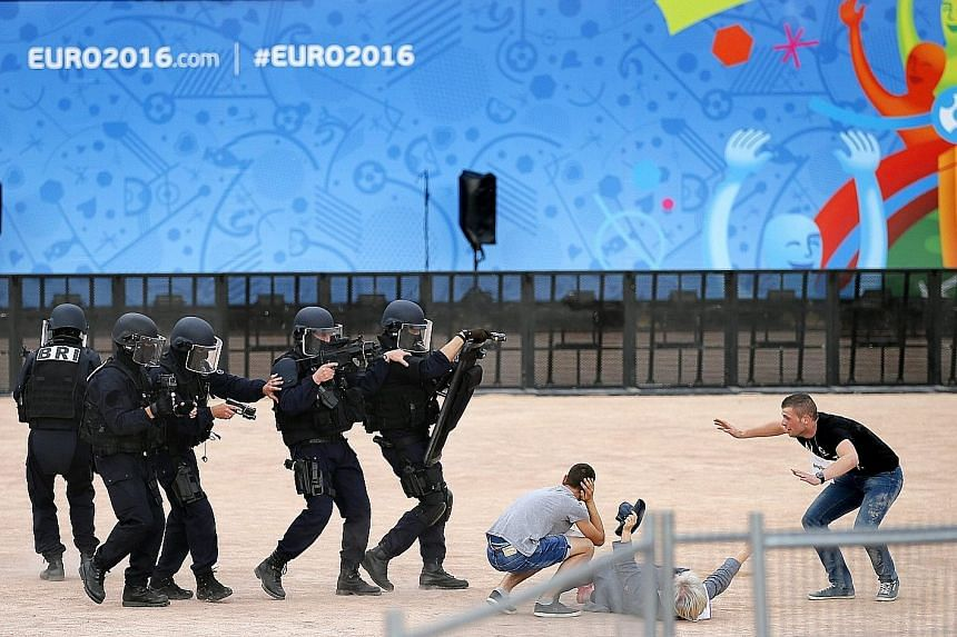 French police officers and volunteers taking part in an anti-terrorism exercise at a fan zone for Euro 2016. France has mobilised 90,000 security personnel for the month-long tournament.