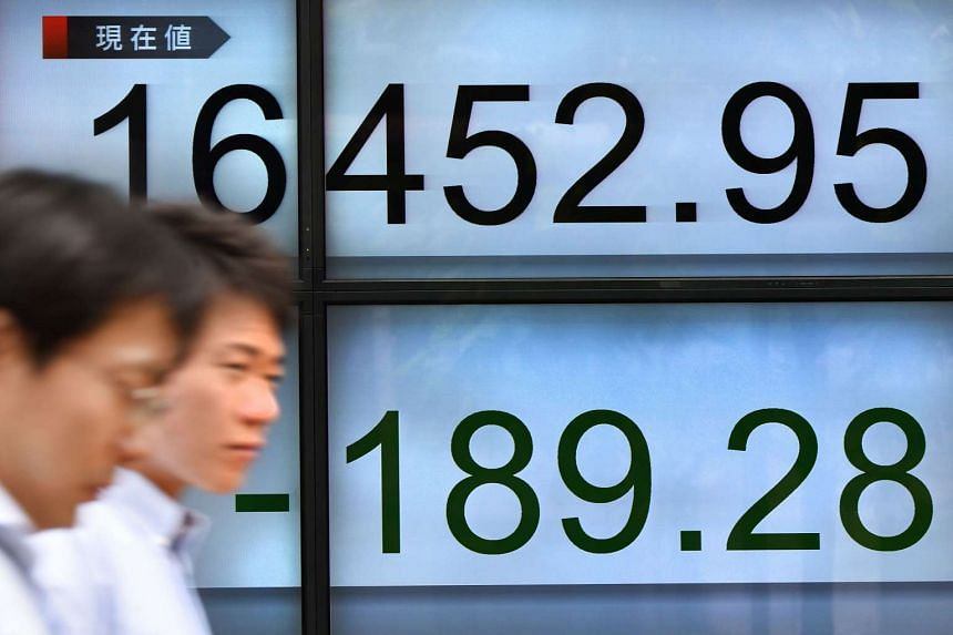 Businessmen walk past an electric quotation board flashing the Nikkei key index of the Tokyo Stock Exchange in Tokyo on June 6.