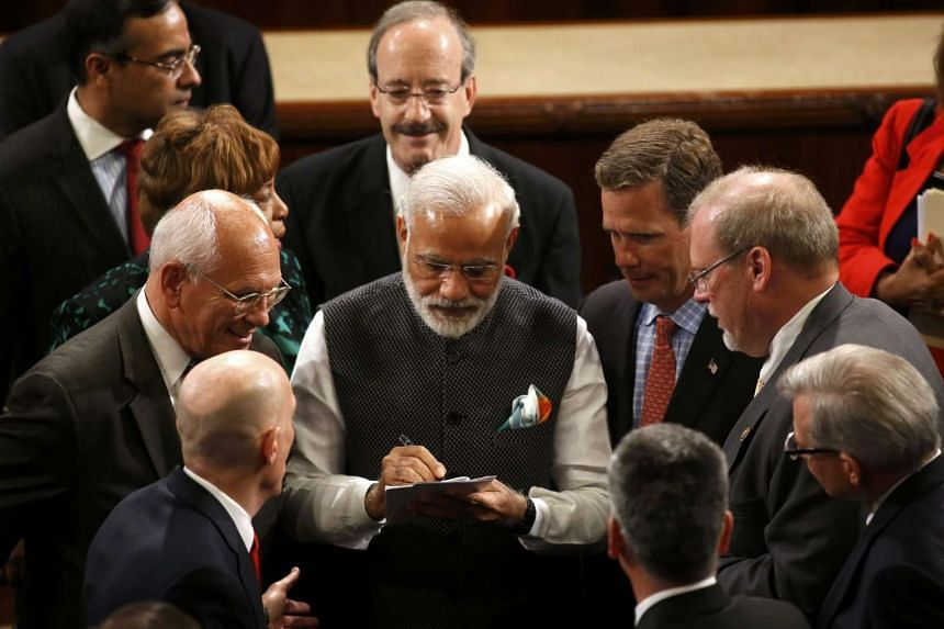 Indian Prime Minister Narendra Modi (centre) signs autographs after addressing a joint meeting of Congress.