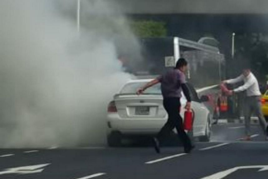 Bus captain Jiang Hong dashing to help the owner of the car put out the fire.