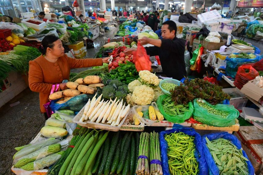 A customer buying vegetables at a market in Fuyang, Anhui province.