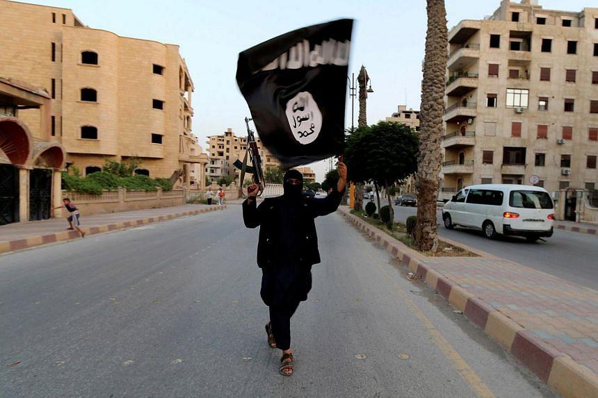 An Islamic State militant waving a flag in Raqqa in 2014.