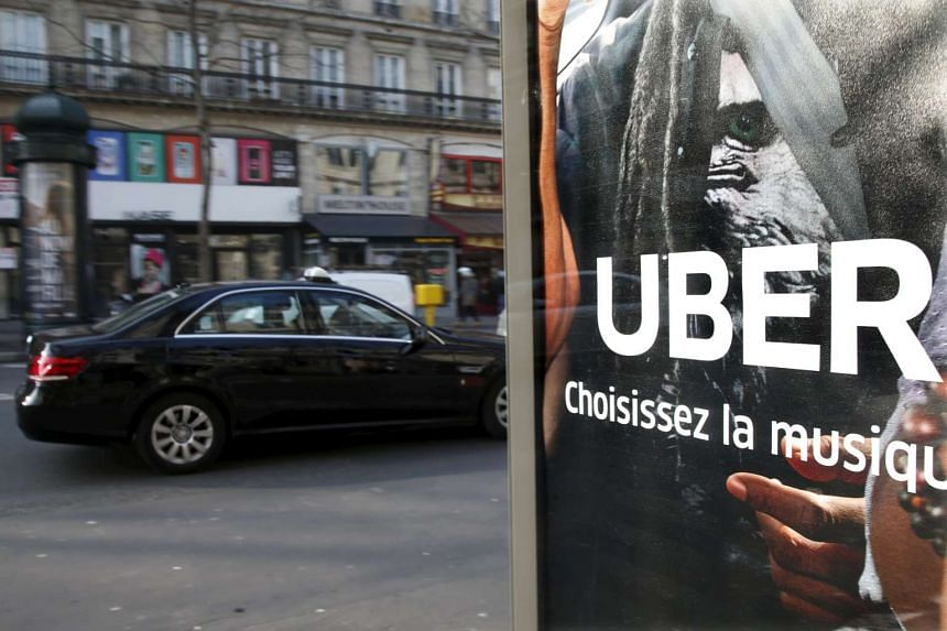 A taxi passes by an advertisement for the Uber car and ride-sharing service displayed on a bus stop in Paris, France.