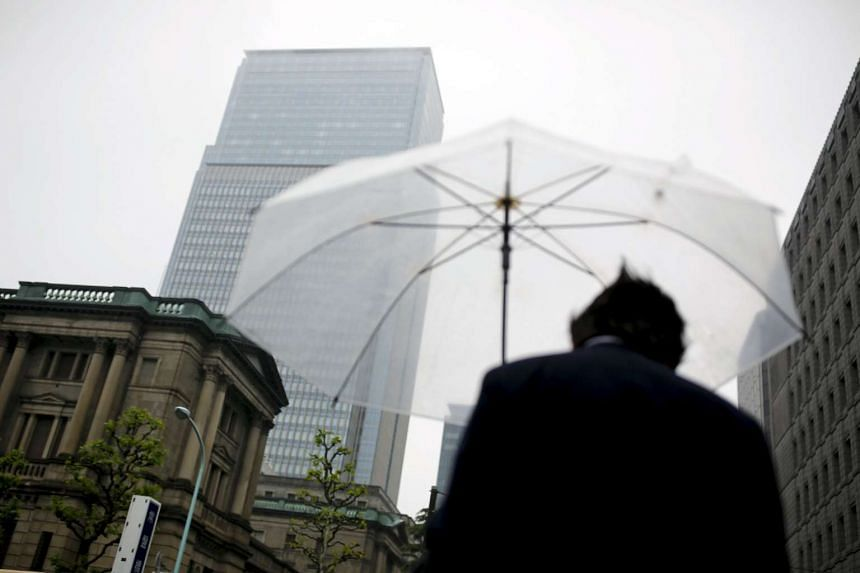 A businessman holds an umbrella as he stands near the Bank of Japan headquarters in Tokyo, Japan, on April 28, 2016.