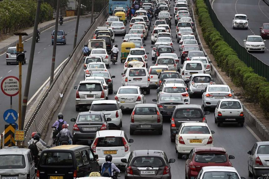 Indian commuters travel in a traffic jam on their way to Gurgaon from New Delhi on May 3, 2016.