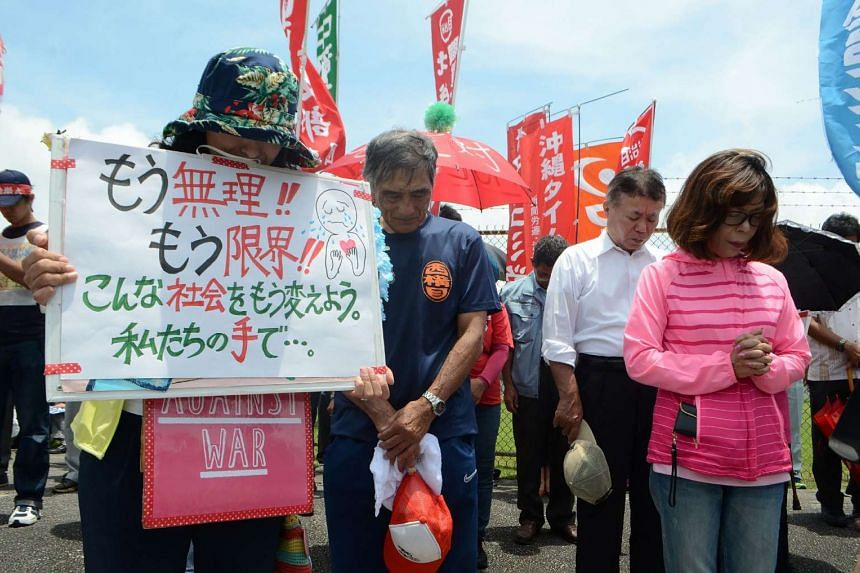 People offer a silent prayer in front of the US Kadena Air Base in Cyatan, Okinawa prefecture, to protest against the US military presence in Okinawa, on May 21, 2016.