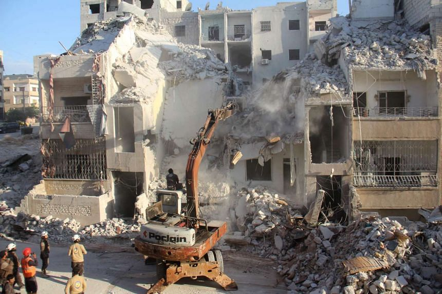 Syrian Civil Defence members search on May 31, 2016, for survivors amid the rubble following reported Russian air strikes the previous night on the Syrian northwestern city of Idlib.