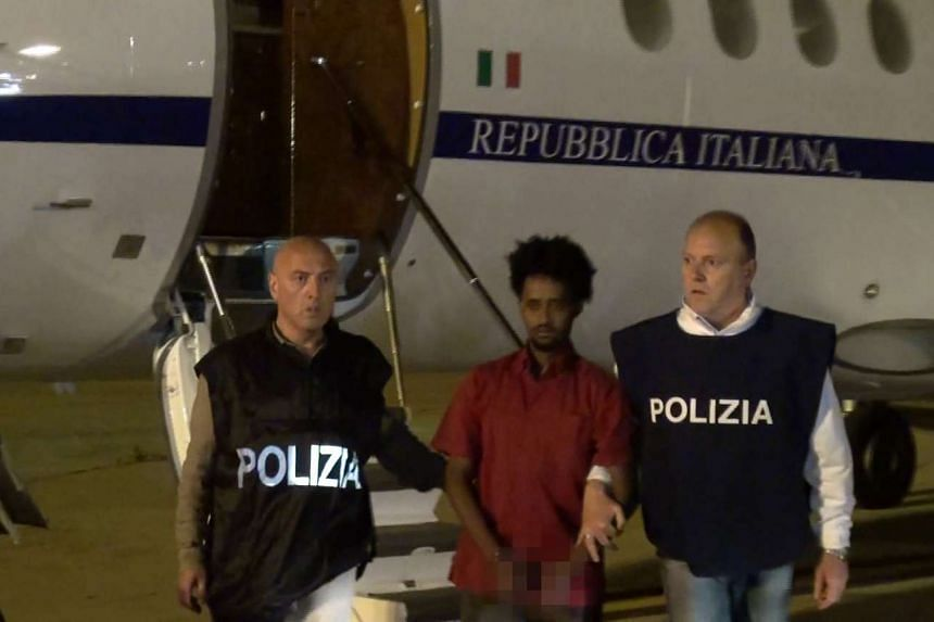 Medhane Yehdego Mered, an Eritrean suspected of controlling a migrant trafficking network, escorted by policemen upon his extradition from Sudan to Italy on June 6, 2016.