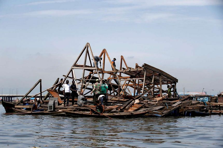 Residents work to dismantle the Makoko floating school after it collapsed in the Makoko fishing community on the Lagos lagoon, Nigeria on June 8, 2016.