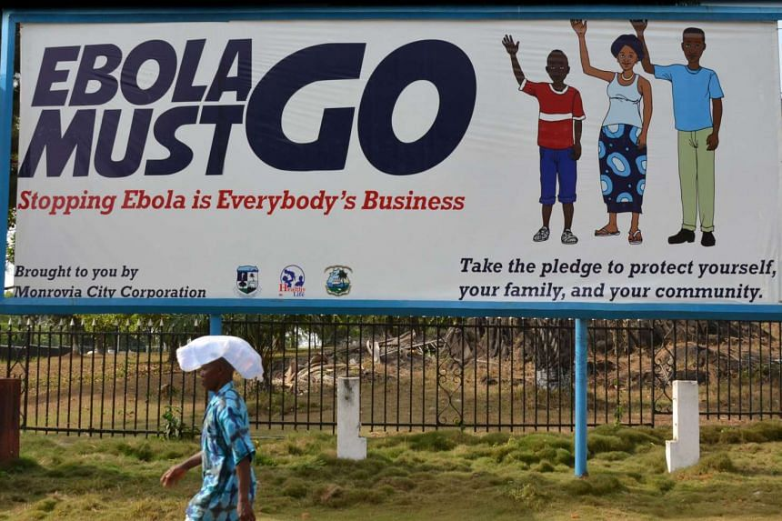 """A man walking past an ebola campaign banner with the slogan """"Ebola Must GO"""" in Monrovia on Feb 23, 2015."""