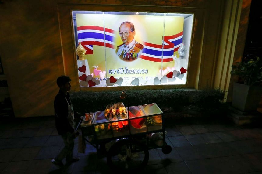 A man pushes a cart as he walks in front of a painting of Thailand's King Bhumibol Adulyadej in Bangkok, Thailand, June 6.
