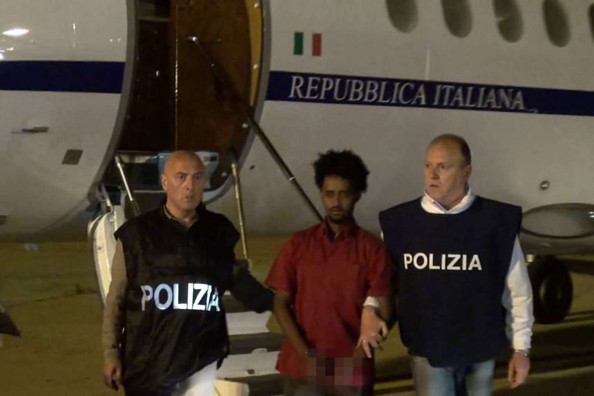 Medhanie Yehdego Mered, 35, is escorted by policemen upon his extradition from Sudan to Italy.