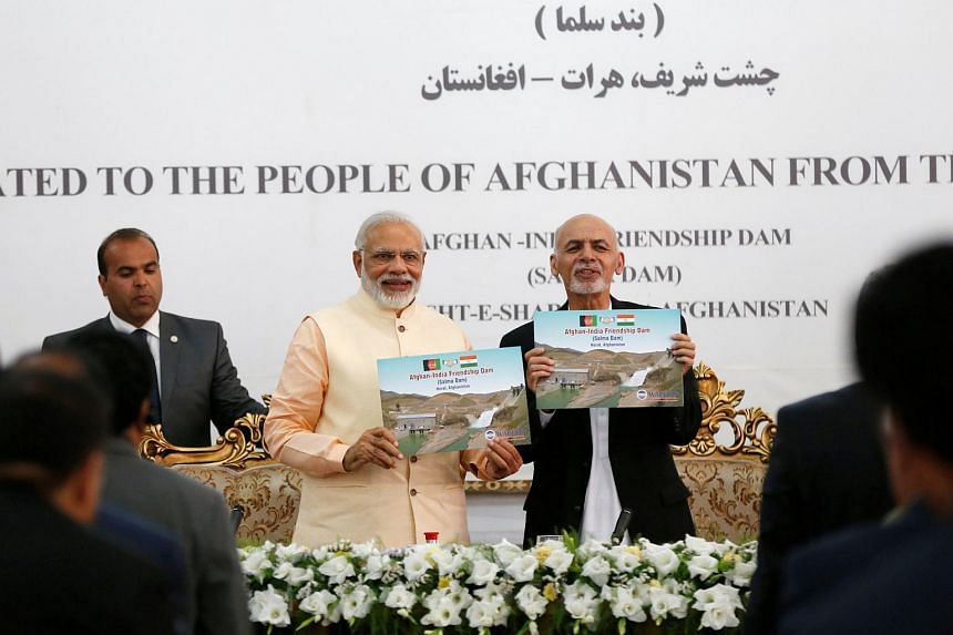 India's Prime Minister Narendra Modi (left) and Afghanistan's President Ashraf Ghani showing pictures of the Salma Dam after its inauguration on June 4.