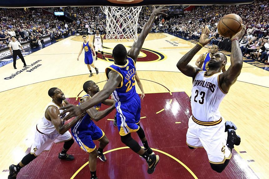 Cleveland Cavaliers forward LeBron James (right) goes for the basket as Golden State Warriors forward Draymond Green (centre) defends.