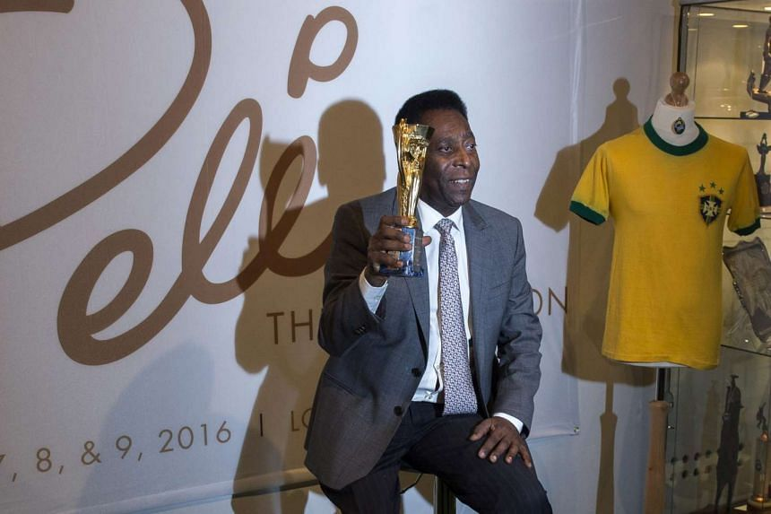 Brazilian soccer legend Pele poses with a replica of the Jules Rimet Trophy during an auction preview.
