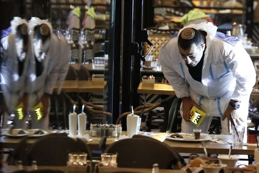 Israeli forensic police inspect a restaurant following the attack.