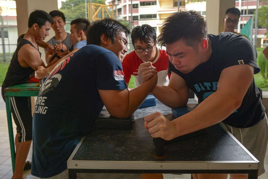 Singapore Armwrestling captain Mr Low (left) and vice-captain Tay Jia Jun fighting it out at a training session. Mr Low is Singapore's most successful arm-wrestler with about 30 gold medals to his name.