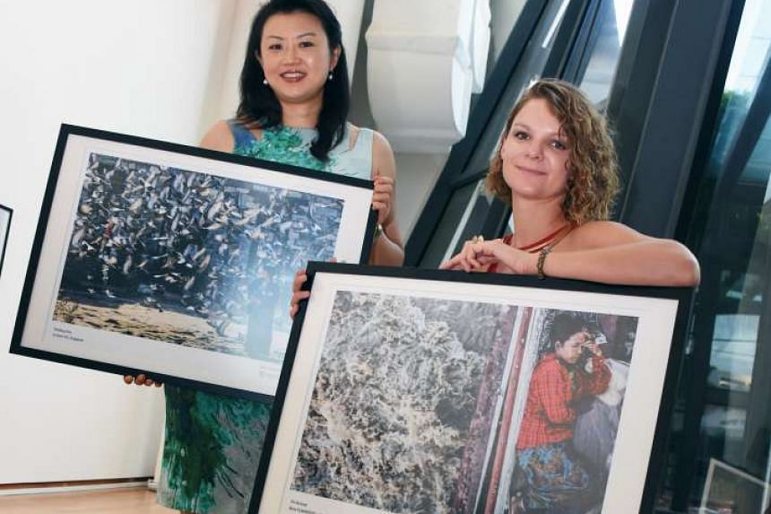 Ms Lee and Ms Tilmantaite with their winning shots, selected from more than 1,500 entries submitted by professional and budding photographers from 50 Asef partner countries.