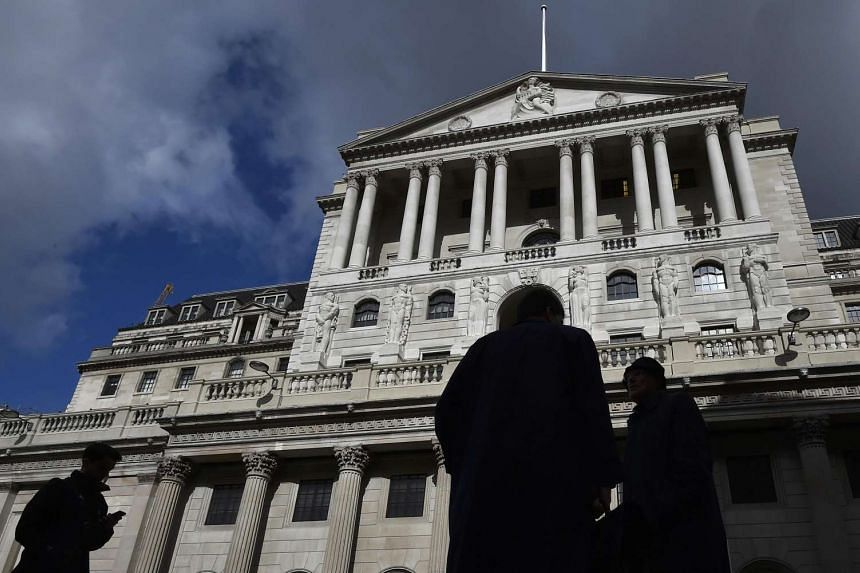 City workers walk past the Bank of England in the City of London, Britain, March 29.