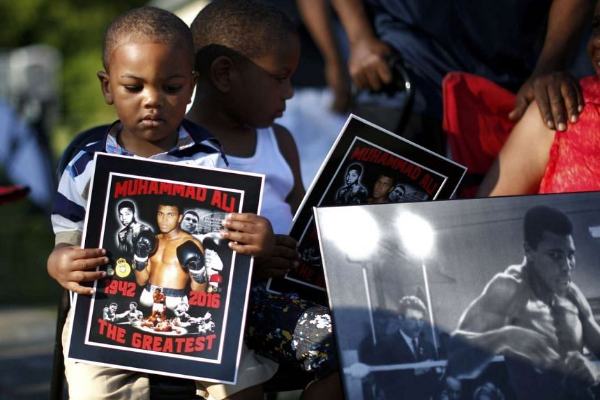 Brandon Liggons (left) holds an image of Muhammad Ali during the funeral procession for the three-time heavyweight boxing champion in Louisville, Kentucky, on June 10, 2016.