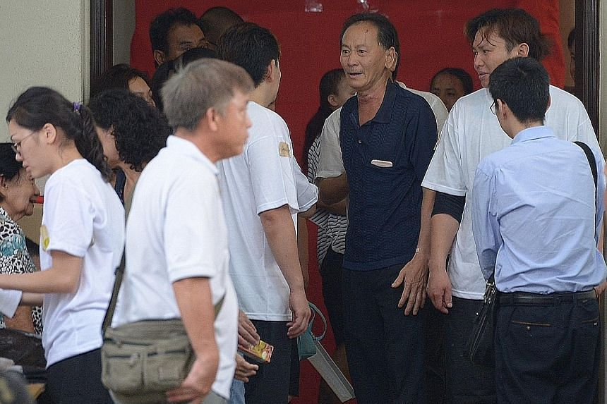 """Mr Ong (centre), husband of Madam Seow, attending to mourners at his wife's wake yesterday. A female employee of Mr Ong and Madam Seow described them as good bosses and said Madam Seow """"takes care of us very much""""."""