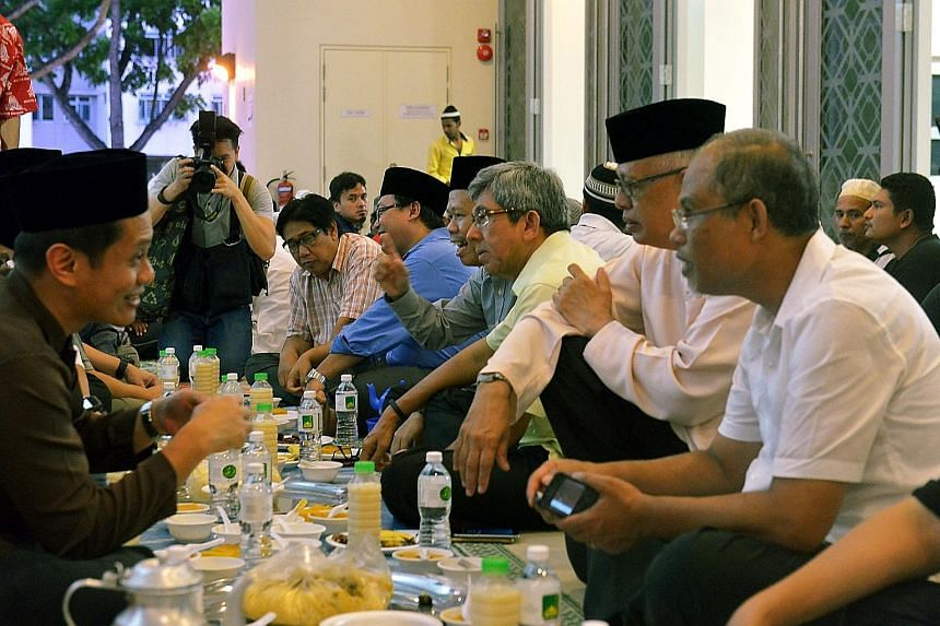 Environment and Water Resources Minister Masagos Zulkifli (right) and Dr Yaacob (third from right) breaking fast with U Care members at Al-Ansar Mosque yesterday.