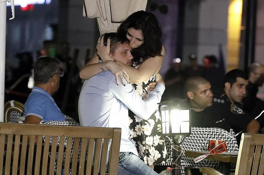 Israelis comforting each other following the shooting attack at a shopping and dining complex in Tel Aviv on Wednesday. At least four people were killed and several wounded in the shooting spree.