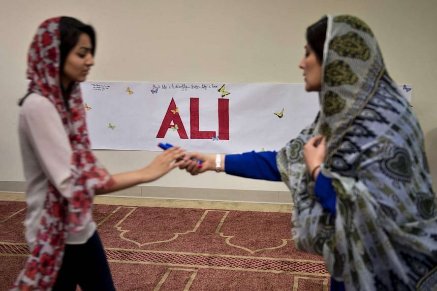 Women preparing to write quotes by Muhammad Ali before an interfaith service at the Louisville Islamic Centre on June 5.