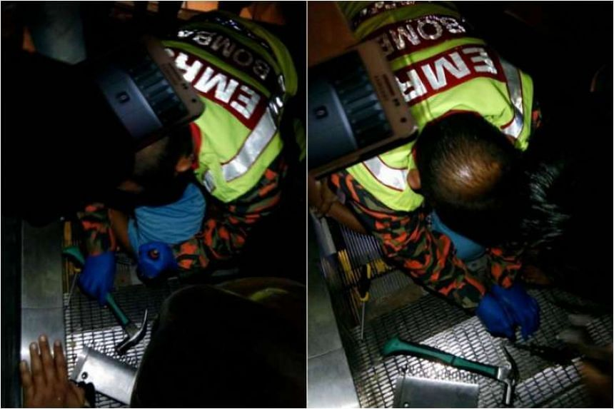 Officers from Malaysia's Emergency Rescue Service team working to free the boy from the escalator.
