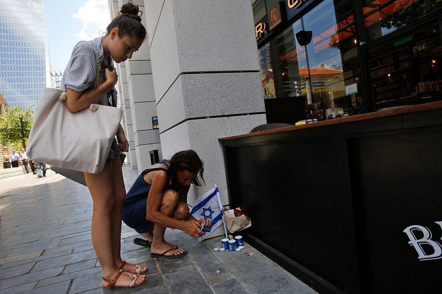 Israeli passers-by light candles on June 9 next to the restaurant that was targeted in the shooting attack in Tel Aviv.