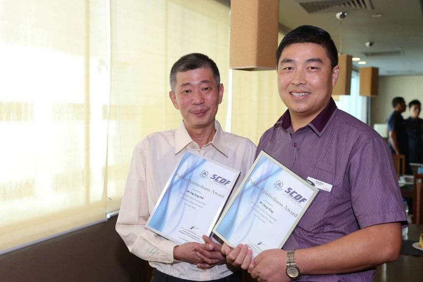 SBS Transitbus driverJiang Hong (right) and ComfortDelGro taxi driverOng Kong Poh received the Public Spiritedness Award for helping to put outa car fire along Farrer Road on Monday (June 6).