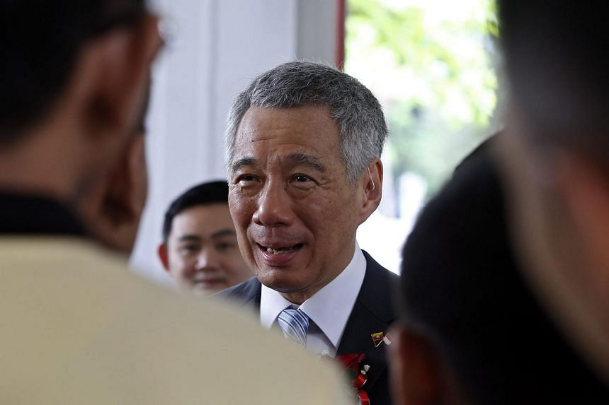 PM Lee Hsien Loong (centre), who is on an official three-day visit to Myanmar, talks with students during the opening ceremony of the Singapore-Myanmar Vocational Training Institute in Yangon, Myanmar, June 9.