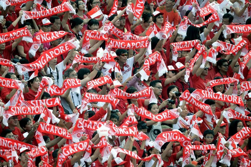 Spectators holding up the Singapore banner during the SG50 National Day Parade 2015 at the Padang.