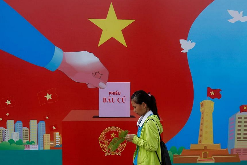 A girl walks past a poster promoting the 14th National Assembly election on a street in Hanoi, Vietnam on May 20.
