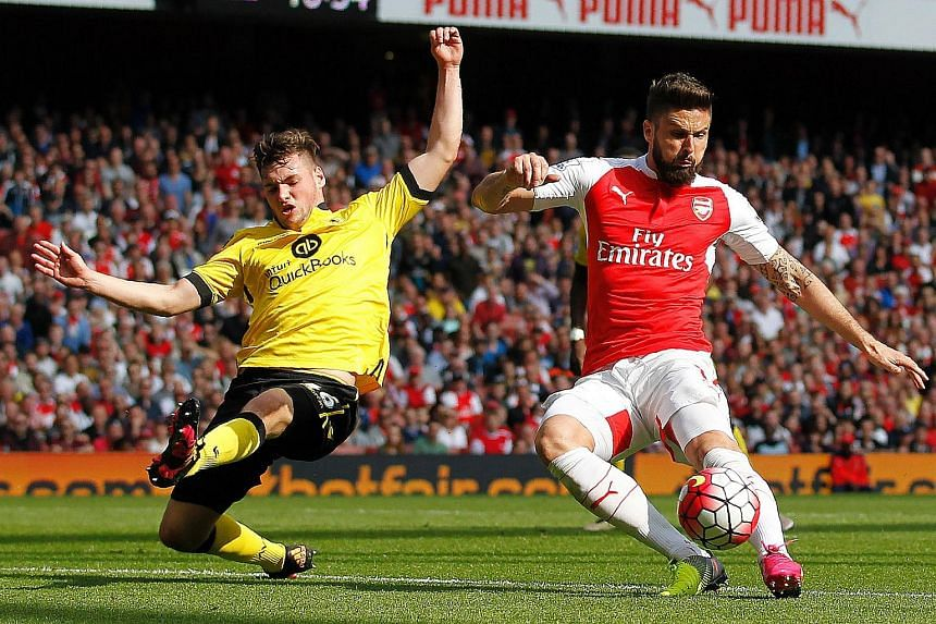 Arsenal's French striker Olivier Giroud (right) shoots past Aston Villa's defender Kevin Toner to score his team's second goal during the EPL football match in London on May 15.