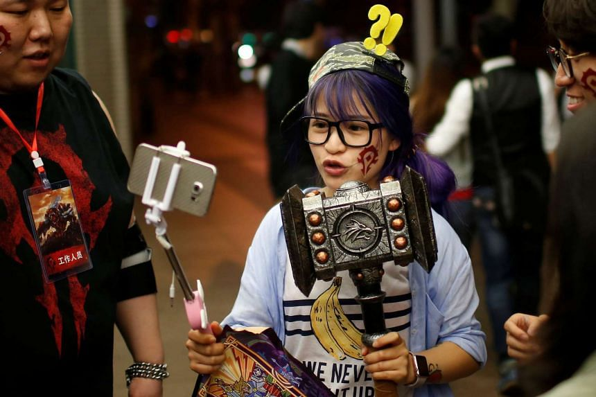 A fan in costume livestreams her participation during China's premiere of the Warcraft film at a theatre in Shanghai.