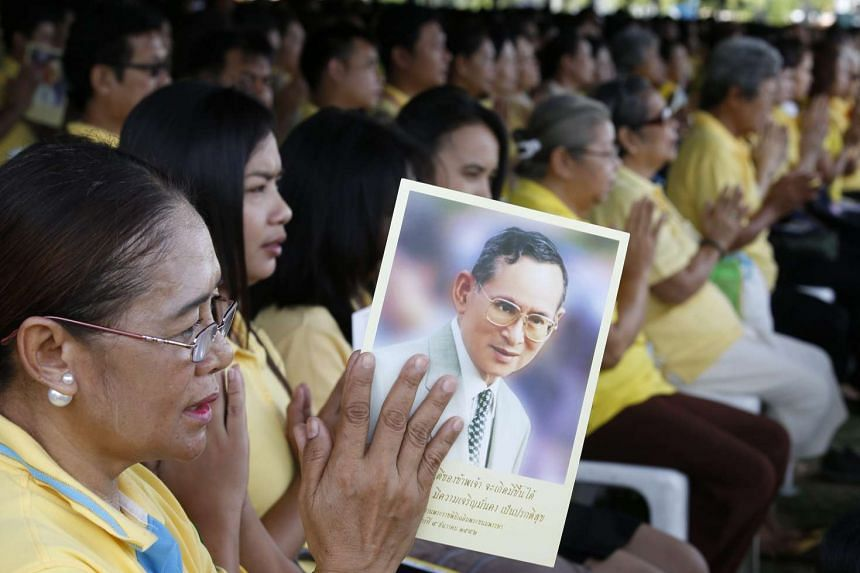 Thais in yellow shirts - yellow is their King's official colour - praying for King Bhumibol Adulyadej during a celebration of the monarch's 70th anniversary of ascension to the throne. The celebration took place yesterday at the Royal Ground near the