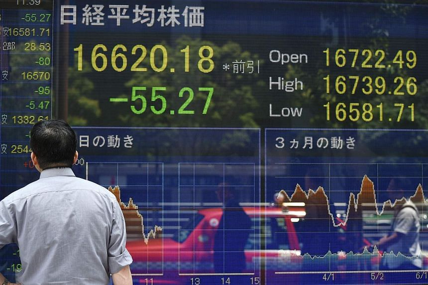 A pedestrian looking at an electronic stock board at a securities company in Tokyo on June 8.