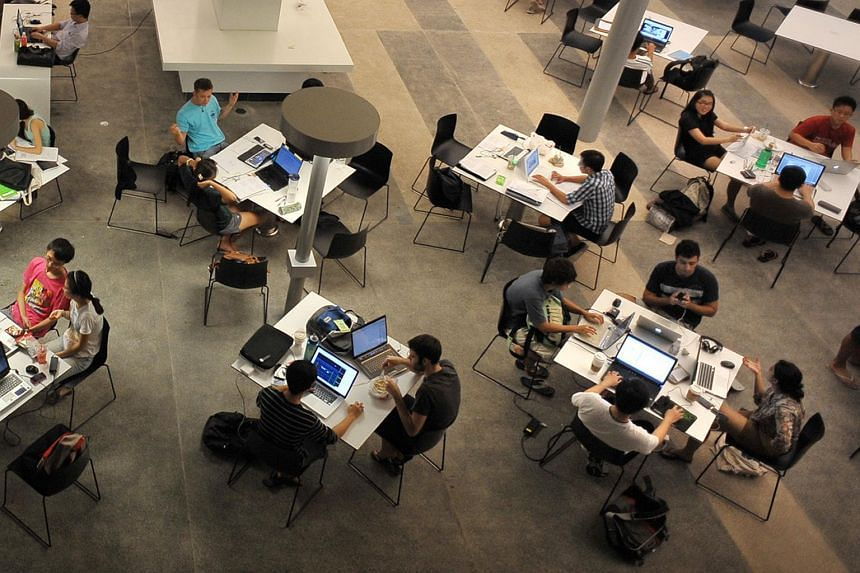NUS students working with their laptops at a study area on campus.