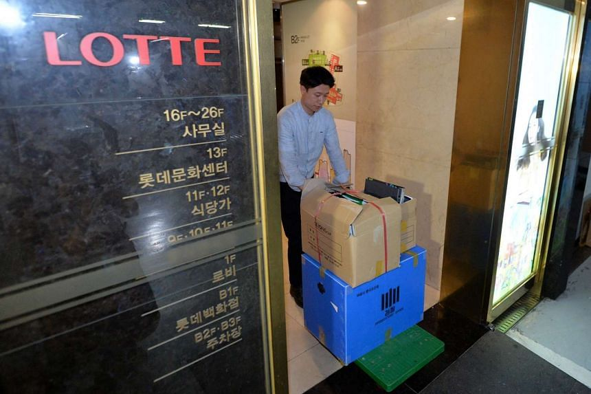 An investigator from the prosecution office carries boxes containing confiscated articles at Lotte Group's headquarters in Seoul, South Korea, on June 10, 2016.