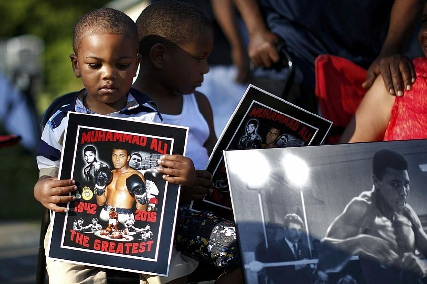 Two-year-old Brandon Liggons holding an image of Ali during the funeral procession for the three-time heavyweight boxing champion in Louisville yesterday.