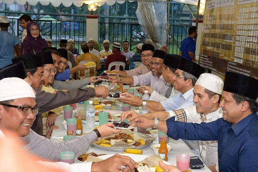 Minister-in-charge of Muslim Affairs Yaacob Ibrahim (third from right) breaking fast with others at the Sallim Mattar Mosque near Aljunied yesterday evening during the holy Muslim month of Ramadan. With a capacity of 1,000, the mosque is popular with
